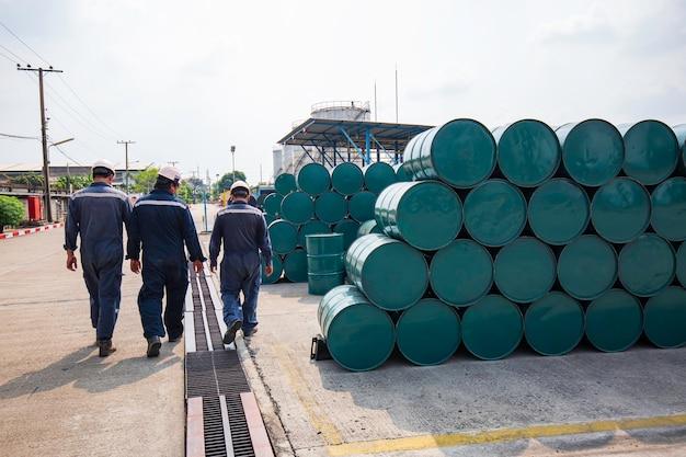 Barili di petrolio di ispezione del lavoro maschile fusti verdi o chimici impilati orizzontalmente