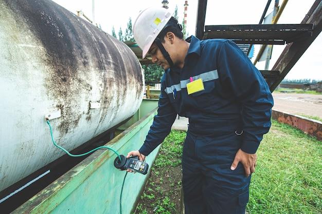 Il lavoratore maschio è per l'ispezione che mette a terra la parte superiore della piastra del serbatoio orizzontale del serbatoio di stoccaggio