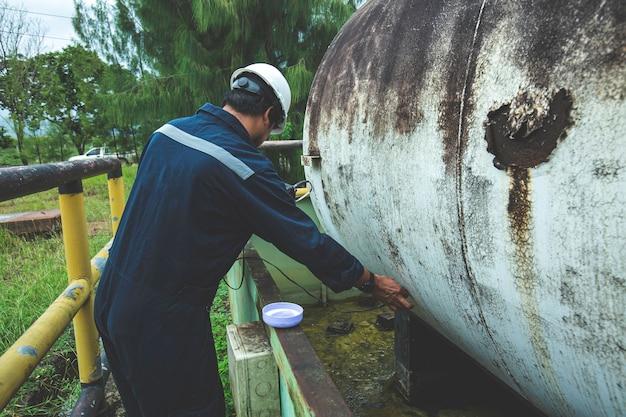 Il lavoratore maschio è per l'ispezione della parte superiore del piatto orizzontale del serbatoio di spessore ultrasonico del serbatoio di stoccaggio