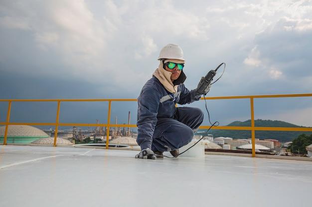Il lavoratore maschio è per l'ispezione della parte superiore della piastra del tetto dello spessore degli ultrasuoni del serbatoio di stoccaggio