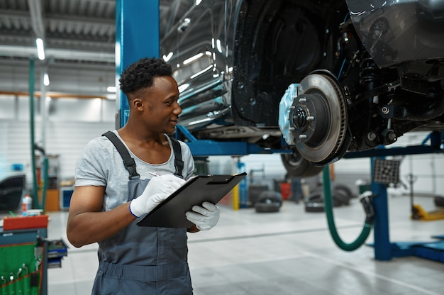 Il lavoratore maschio controlla i freni dell'auto, il servizio auto
