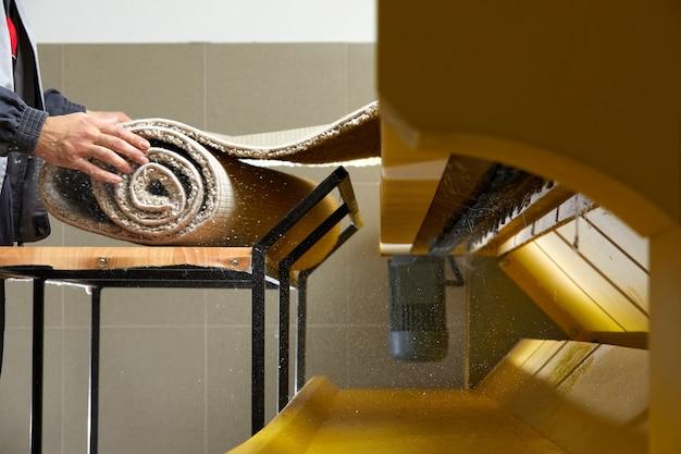 Operaio maschio pulizia tappeto su attrezzature lavatrice automatica e asciugatrice nella lavanderia