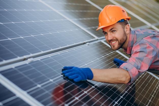 Operaio maschio che pulisce i pannelli solari