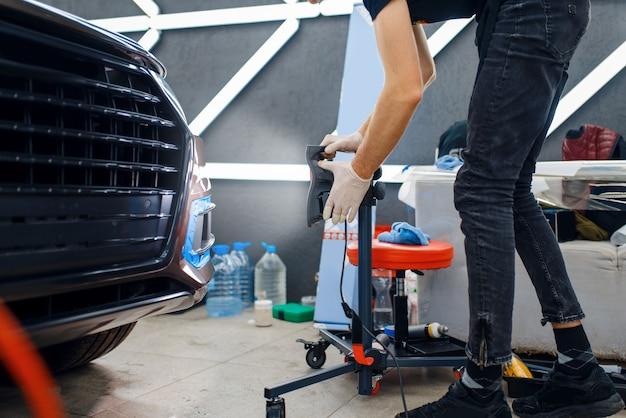 Il lavoratore di sesso maschile asciuga la pellicola di protezione dell'auto utilizzando una lampada potente. installazione di rivestimento che protegge la vernice dell'automobile dai graffi. veicolo in garage, procedura di messa a punto automatica