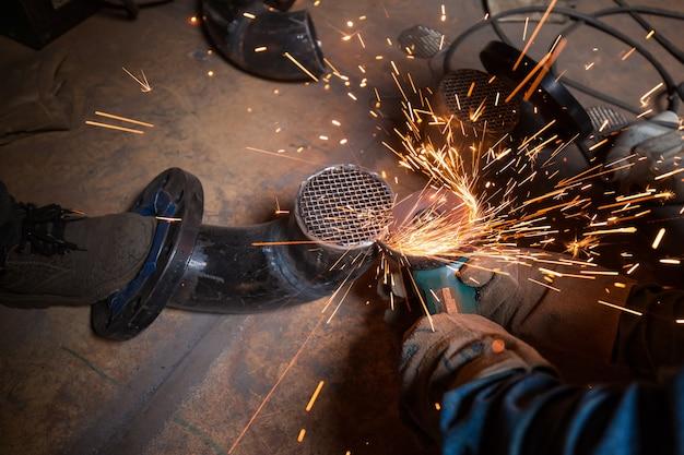 Lavoratore di sesso maschile che rettifica al gomito della conduttura della griglia indossando indumenti protettivi che fissano per petrolio e gas da costruzione industriale o condutture all'interno di spazi ristretti.