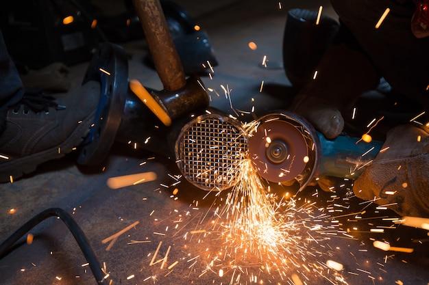 Lavoratore di sesso maschile che rettifica al gomito della conduttura della griglia indossando indumenti protettivi che fissano per l'edilizia industriale petrolio e gas o condutture all'interno di spazi ristretti.