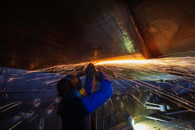 Lavoratore maschio che macina su piastra d'acciaio con flash di scintille da vicino indossa guanti protettivi olio all'interno di spazi ristretti.