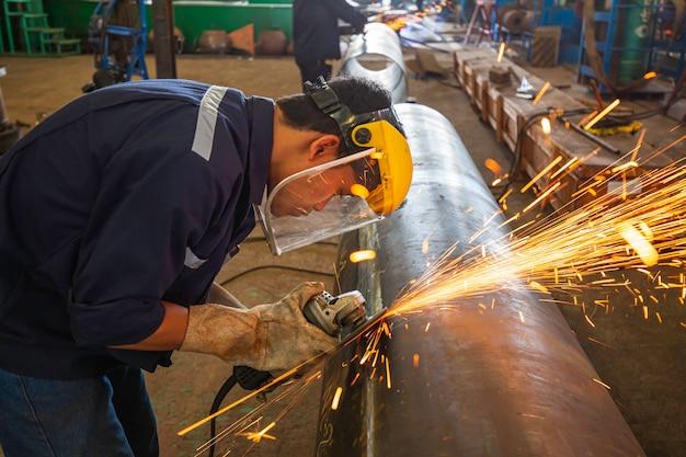 Il lavoratore di sesso maschile che macina su piastra d'acciaio con un lampo di scintille si chiude indossando guanti protettivi
