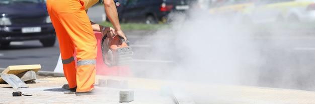 Il lavoratore maschio tiene la taglierina del gas nelle sue mani e taglia il cemento. concetto di lavori stradali di costruzione