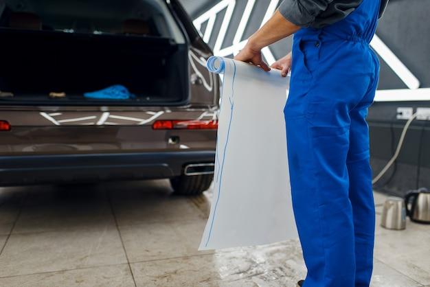 Il lavoratore di sesso maschile tiene il rotolo di pellicola protettiva per l'auto. installazione di rivestimento che protegge la vernice dell'automobile dai graffi. veicolo nuovo in garage, preparazione procedura di messa a punto