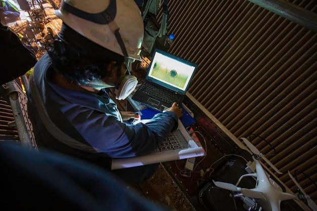 Elicottero drone di ispezione del lavoratore maschio che vola veloce con tubo del forno di scansione della fotocamera digitale confinato