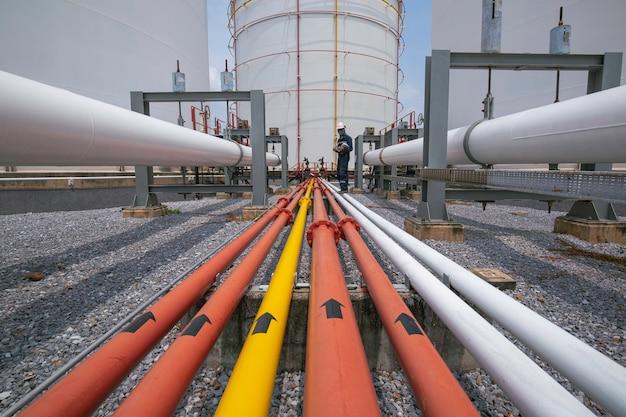 Ispezione del lavoratore di sesso maschile al tubo flangiato dell'industria petrolifera e del gas della conduttura di registrazione del controllo visivo