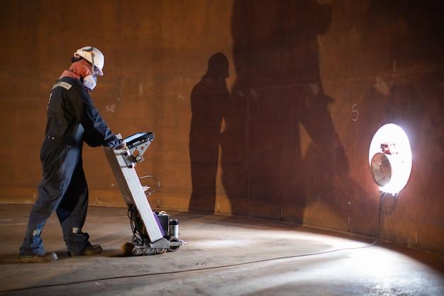 Il serbatoio di scansione del pavimento di ispezione del lavoratore di sesso maschile della parete di ruggine perde spessore della piastra inferiore in confinato