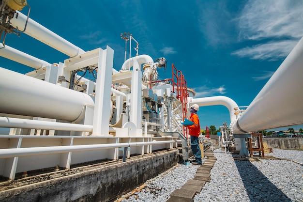 Ispezione del lavoratore di sesso maschile su tubi lunghi in acciaio e gomito del tubo nella fabbrica di petrolio della stazione durante la valvola di raffineria del registro di controllo visivo