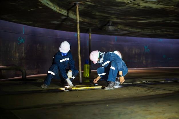 Ispezione del lavoratore maschio prova di vuoto piastra inferiore serbatoio petrolchimico acciaio saldatura perdita specifica interna confinata