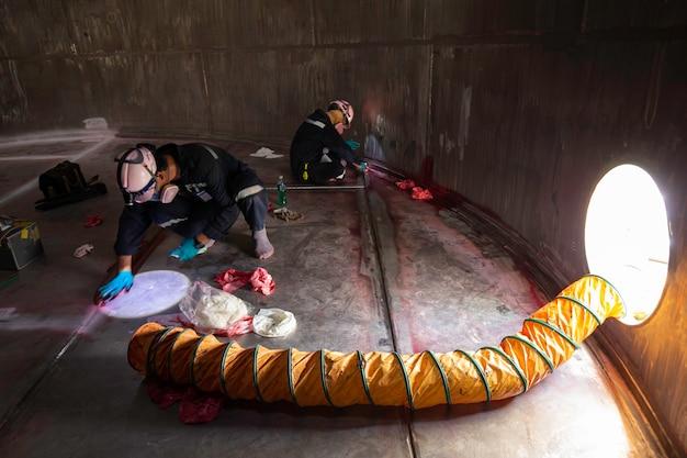 Ispezione del lavoratore maschio sostanze chimiche visive ventilatore in acciaio inossidabile aria fresca nello spazio limitato del serbatoio di stoccaggio