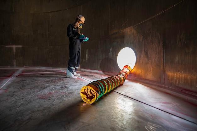 Ispezione del lavoratore di sesso maschile sostanze chimiche visive in acciaio inossidabile ventilatore aria fresca nello spazio limitato del serbatoio di stoccaggio
