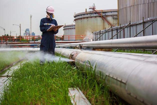 Operaio maschio ispezione visual pipeline olio e gas corrosione ruggine attraverso presa tubo vapore gasdotto perdita di isolamento.