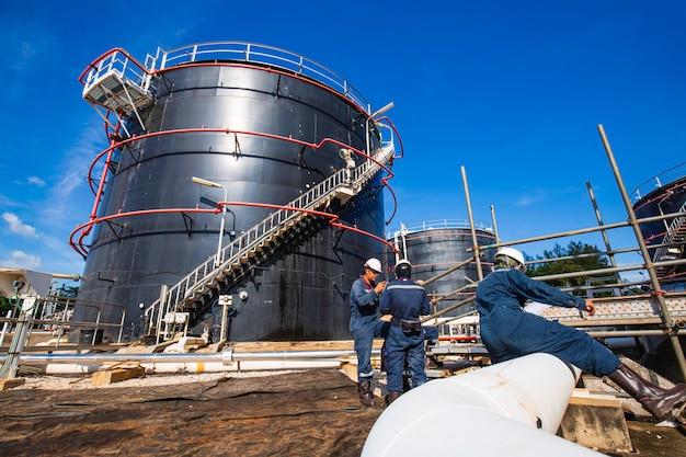 Conduttura visiva di ispezione del lavoratore maschio e petrolio greggio del serbatoio di stoccaggio