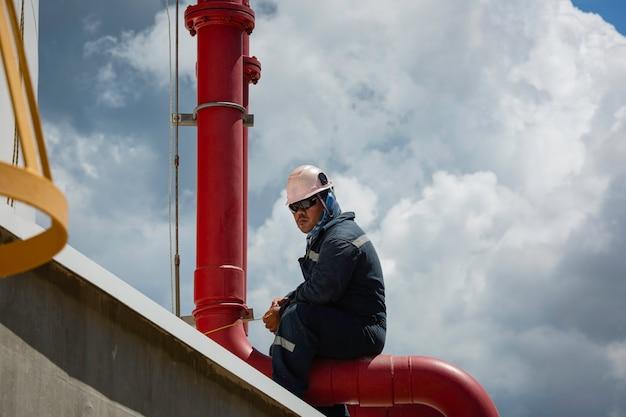 Fondo visivo e cielo blu dell'olio del serbatoio di stoccaggio della conduttura di ispezione del lavoratore maschio.