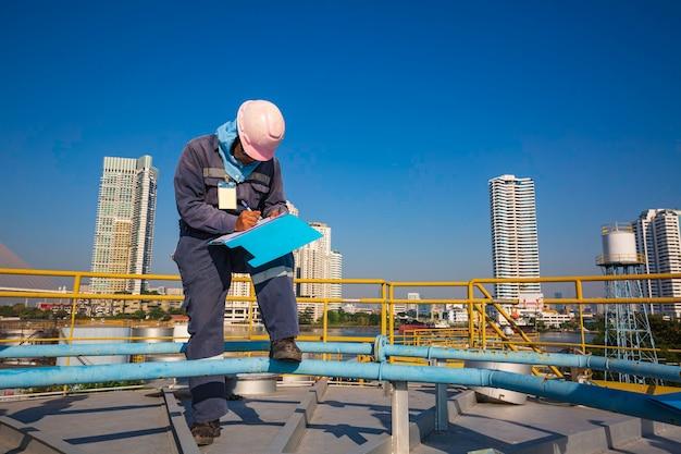 Città e cielo blu del fondo del serbatoio dell'olio del serbatoio di stoccaggio del tetto di ispezione del lavoratore di sesso maschile