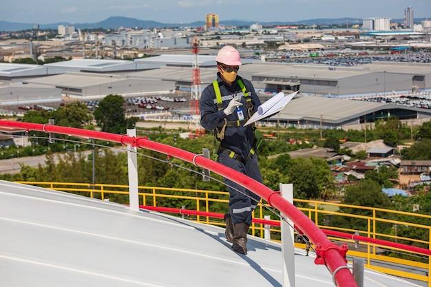 Operaio maschio ispezione visiva tetto serbatoio olio sfondo città e cielo blu.