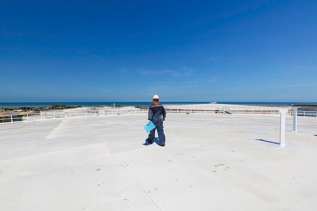 Città e cielo blu del fondo del serbatoio dell'olio del serbatoio di stoccaggio del tetto di ispezione del lavoratore