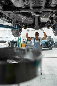 Il lavoratore maschio ispeziona la sospensione dell'auto, il servizio auto