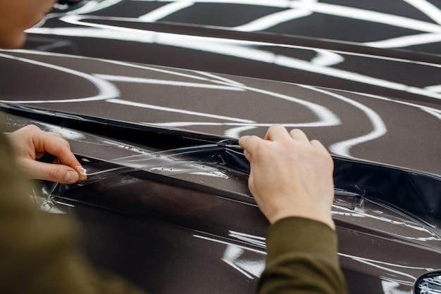Il lavoratore di sesso maschile installa una pellicola protettiva trasparente sul cofano dell'auto. installazione di un rivestimento che protegge la vernice dell'auto dai graffi. veicolo nuovo in garage, procedura di tuning