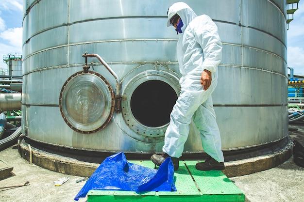 Lavoratore di sesso maschile nel tombino del serbatoio del carburante dell'olio dell'abbigliamento protettivo chimico nell'area dello spazio confinato pericoloso