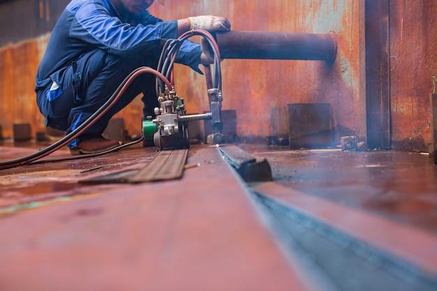 Scintilla di taglio del metallo del lavoratore maschio sul piatto d'acciaio del fondo del serbatoio con il flash della luce di taglio da vicino in uno spazio confinato laterale.