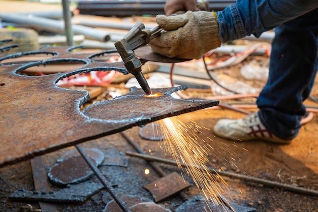 Scintilla di taglio del metallo del lavoratore di sesso maschile sulla piastra d'acciaio del fondo del serbatoio con il flash della luce di taglio da vicino indossare guanti protettivi per le mani.