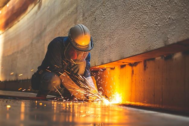 Scintilla di taglio del metallo del lavoratore di sesso maschile sulla piastra d'acciaio del fondo del serbatoio con flash di luce di taglio da vicino indossare guanti protettivi e maschera in uno spazio confinato laterale.