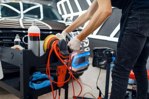 Lavoratore maschio vicino alla cassetta degli attrezzi con lucidatrice e strumenti di lucidatura, dettagli dell'auto. preparazionea prima dell'installazione del rivestimento che protegge la vernice dell'automobile da graffi, messa a punto automatica