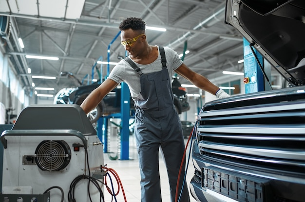 Il lavoratore maschio ricarica il condizionatore d'aria, servizio auto. garage di riparazione di veicoli, uomo in uniforme, interni della stazione automobilistica