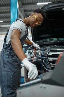 Il lavoratore maschio ricarica il condizionatore d'aria, servizio auto