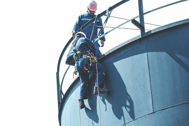 Ispezione di sicurezza dell'altezza di accesso alla fune del lavoratore maschile dell'industria dei serbatoi di petrolio e gas di stoccaggio dello spessore