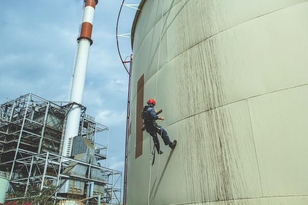 Ispezione di sicurezza dell'altezza di accesso alla fune del lavoratore di sesso maschile dell'industria dei serbatoi di petrolio e gas di stoccaggio dello spessore