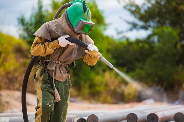 Lavoratore di sesso maschile sabbiatura processo pulizia superficie della conduttura su acciaio prima della verniciatura in fabbrica.