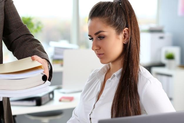 Lavoratore maschio mostra pacco di documenti alla donna d'affari impegnata