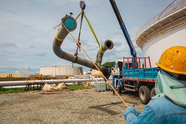 Operaio maschio il fromboliere al lavoro con la gru. scarico dalla gru dell'olio della conduttura di produzione e dell'attrezzatura della valvola.