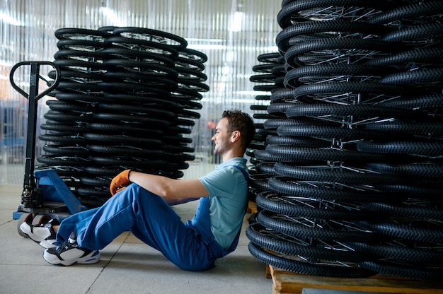 Lavoratore di sesso maschile presso la pila di ruote di bicicletta su un pallet in fabbrica. linea di assemblaggio cerchi bici in officina, installazione componenti ciclo, tecnologia moderna