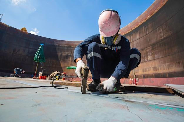 Lavoratore maschio prova serbatoio in acciaio saldatura testa a testa piastra inferiore in carbonio del serbatoio di stoccaggio olio sfondo bianco contrasto del campo magnetico test