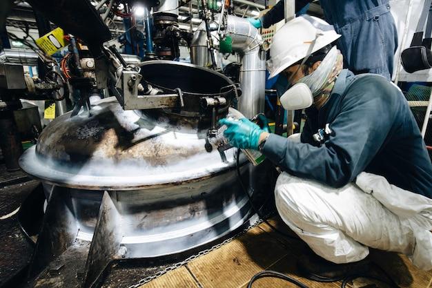 Lavoratore maschio prova serbatoio in acciaio saldatura testa a testa guscio in carbonio piastra del serbatoio di stoccaggio olio motore sfondo contrasto bianco della prova del campo magnetico.