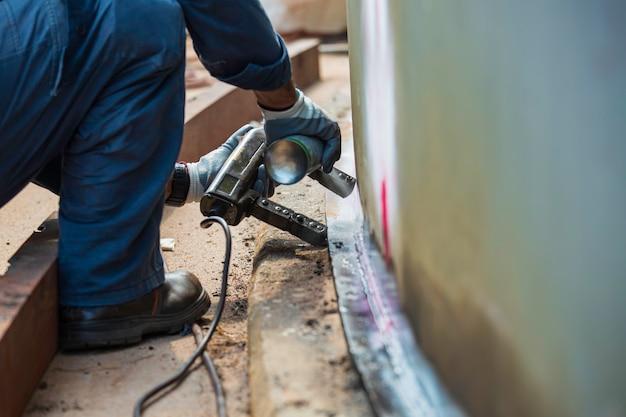 Lavoratore maschio prova serbatoio in acciaio rivestimento di saldatura di testa guscio in carbonio piastra del serbatoio di stoccaggio olio sfondo bianco contrasto del campo magnetico test