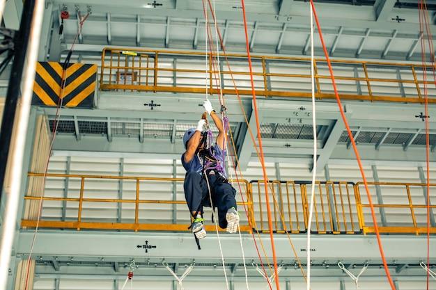 Accesso di trasferimento da corda a corda per l'addestramento del lavoratore di sesso maschile nel lavoro ad alto livello