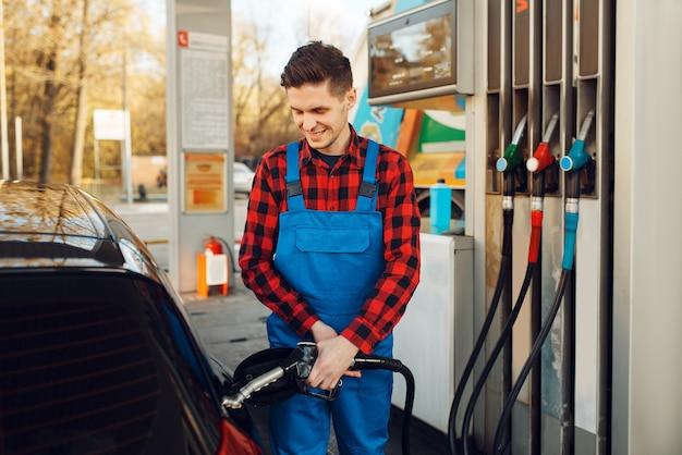 Lavoratore di sesso maschile in uniforme alimenta auto sulla stazione di servizio, rifornimento di carburante. servizio di rifornimento benzina, benzina o gasolio