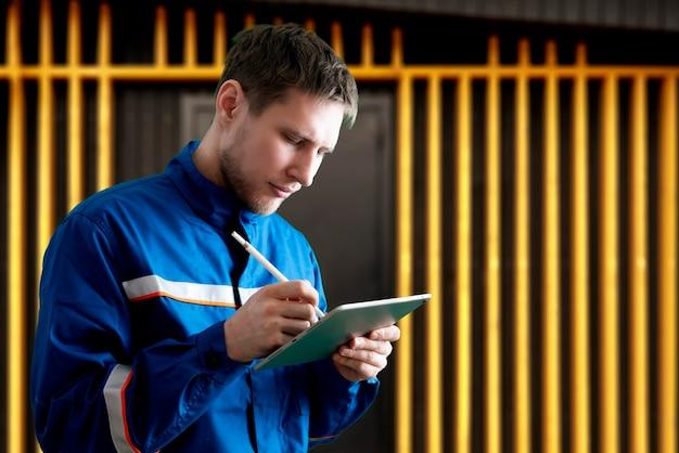 Un lavoratore di sesso maschile in uniforme che tiene e usa un tablet