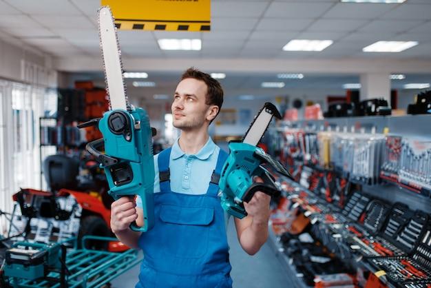 Il lavoratore maschio in uniforme tiene le motoseghe grandi e piccole nel negozio di utensili. scelta di attrezzature professionali in ferramenta, supermercato di strumenti