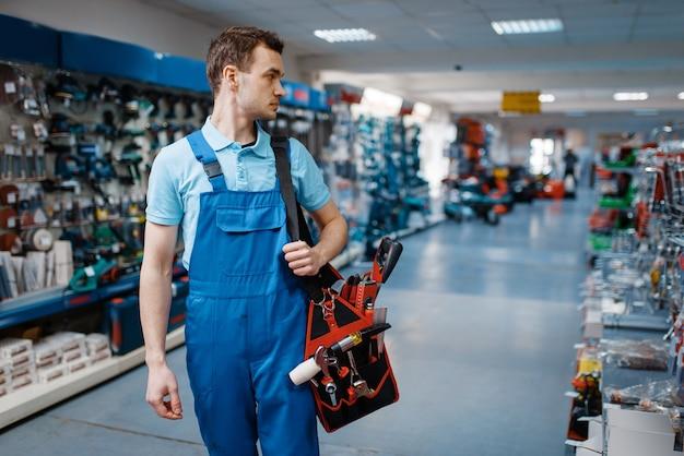 Il lavoratore di sesso maschile in uniforme tiene la cassetta degli attrezzi nel negozio di utensili. scelta di attrezzature professionali nel negozio di ferramenta